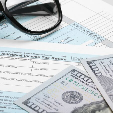 taxable income: US Tax Form 1040 with 100 dollars and glasses