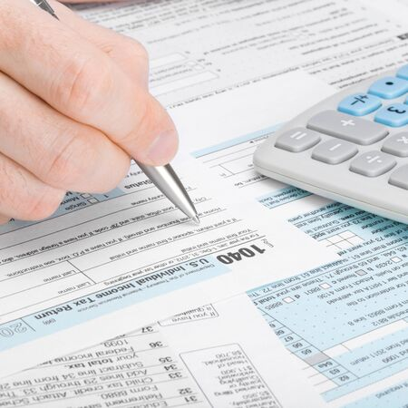 taxable: Man filling out 1040 tax form Stock Photo