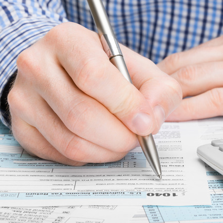 taxable: Male filling out ax form with pen Stock Photo