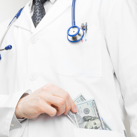 doctor putting money: Doctor putting money into his pocket