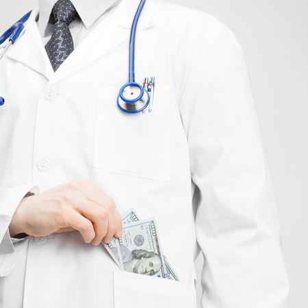 doctor money: Doctor putting money into his pocket