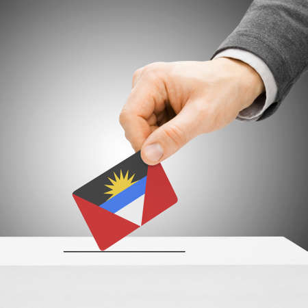 political system: Voting concept - Male inserting flag into ballot box - Antigua and Barbuda