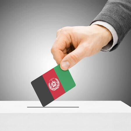 political system: Voting concept - Male inserting flag into ballot box - Afghanistan Stock Photo