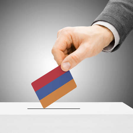 electoral system: Voting concept - Male inserting flag into ballot box - Armenia Stock Photo