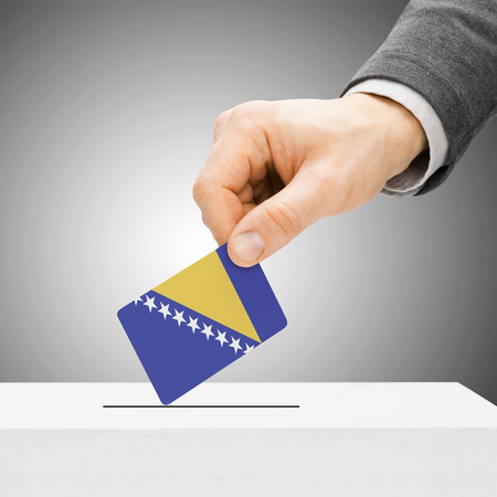 polling booth: Voting concept - Male inserting flag into ballot box - Bosnia and Herzegovina