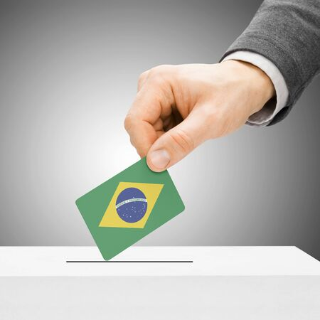 polling booth: Voting concept - Male inserting flag into ballot box - Brazil