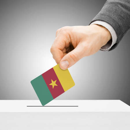 polling booth: Voting concept - Male inserting flag into ballot box - Cameroon Stock Photo