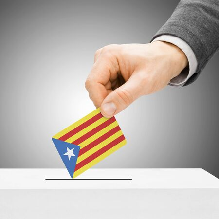 political system: Voting concept - Male inserting flag into ballot box - Catalonia Stock Photo