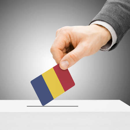 chadian: Voting concept - Male inserting flag into ballot box - Chad Stock Photo
