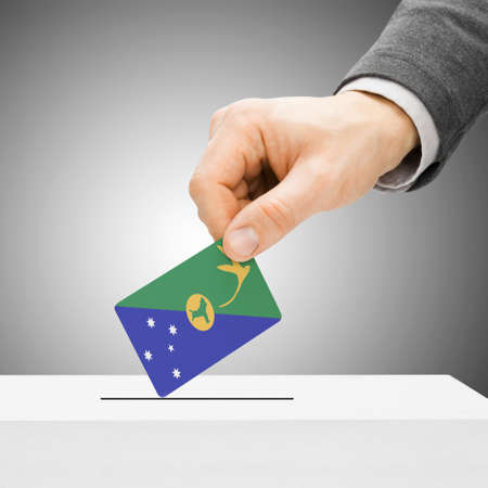 plebiscite: Voting concept - Male inserting flag into ballot box - Christmas Island
