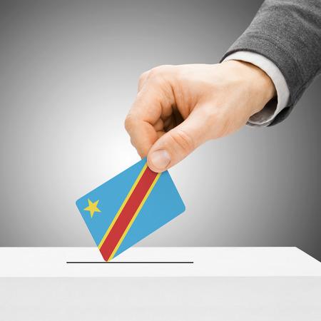 political system: Voting concept - Male inserting flag into ballot box - Democratic Republic of the Congo