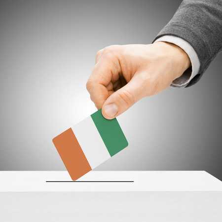 political system: Voting concept - Male inserting flag into ballot box - Cote dIvoire - Ivory Coast