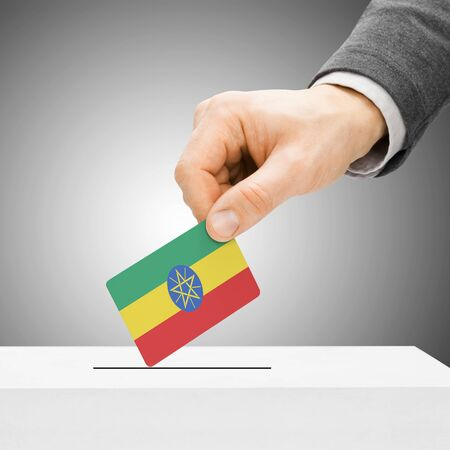 political system: Voting concept - Male inserting flag into ballot box - Ethiopia Stock Photo