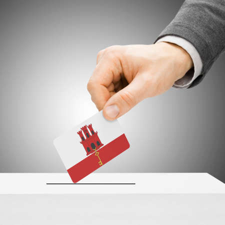 plebiscite: Voting concept - Male inserting flag into ballot box - Gibraltar Stock Photo