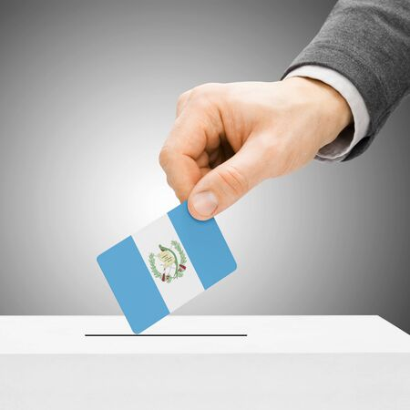 political system: Voting concept - Male inserting flag into ballot box - Guatemala Stock Photo