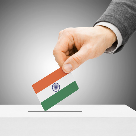 political system: Voting concept - Male inserting flag into ballot box - India Stock Photo