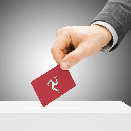 plebiscite: Voting concept - Male inserting flag into ballot box - Isle of Man Stock Photo