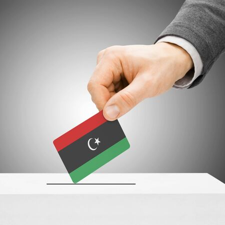 political system: Voting concept - Male inserting flag into ballot box - Libya