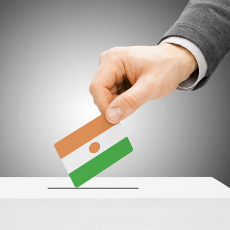 political system: Voting concept - Male inserting flag into ballot box - Niger Stock Photo