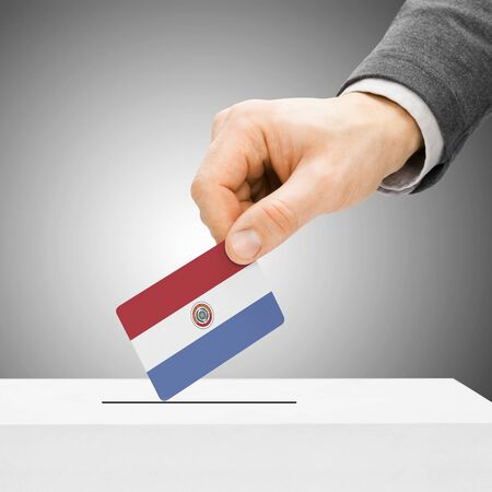 political system: Voting concept - Male inserting flag into ballot box - Paraguay