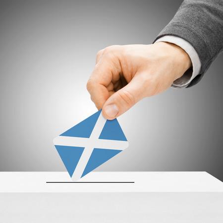 scottish parliament: Voting concept - Male inserting flag into ballot box - Scotland Stock Photo