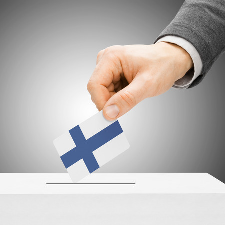 political system: Voting concept - Male inserting flag into ballot box - Finland