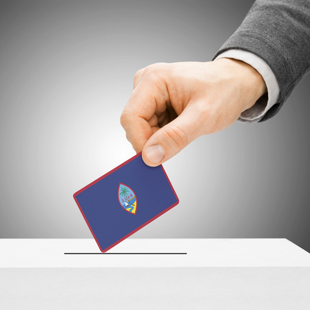 political system: Voting concept - Male inserting flag into ballot box - Guam Stock Photo
