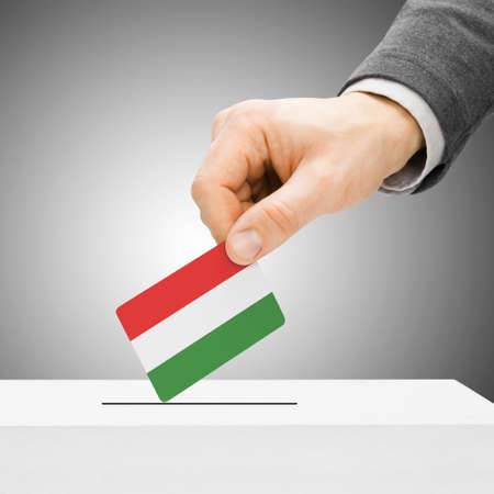 political system: Voting concept - Male inserting flag into ballot box - Hungary