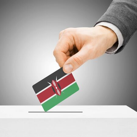 political system: Voting concept - Male inserting flag into ballot box - Kenya Stock Photo