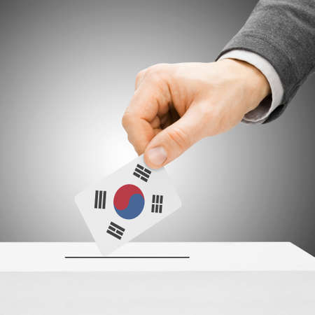 political system: Voting concept - Male inserting flag into ballot box - South Korea