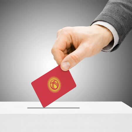 political system: Voting concept - Male inserting flag into ballot box - Kyrgyzstan Stock Photo