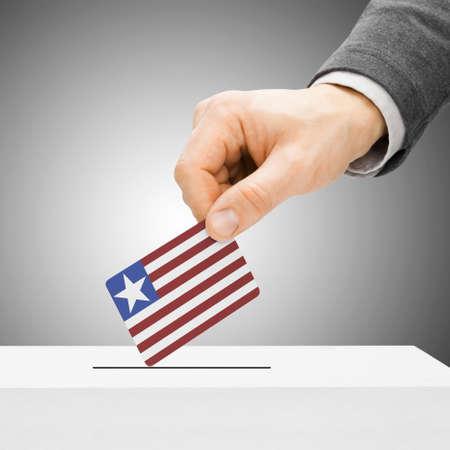 political system: Voting concept - Male inserting flag into ballot box - Liberia