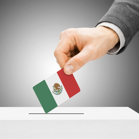 Voting concept - Male inserting flag into ballot box - Mexico Imagens