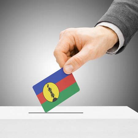 new caledonia: Voting concept - Male inserting flag into ballot box - New Caledonia Stock Photo