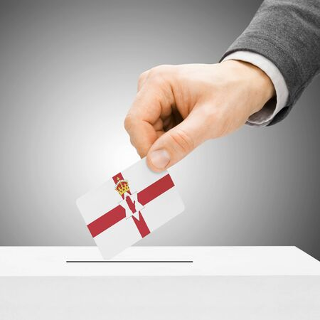 electoral system: Voting concept - Male inserting flag into ballot box - Northern Ireland Stock Photo