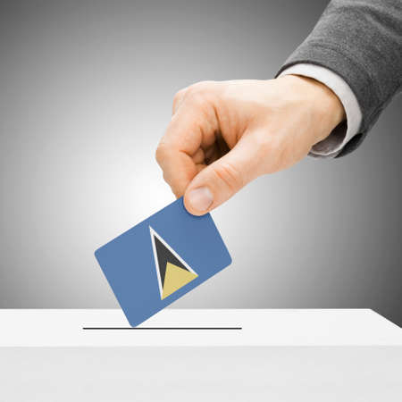 polling booth: Voting concept - Male inserting flag into ballot box - Saint Lucia Stock Photo