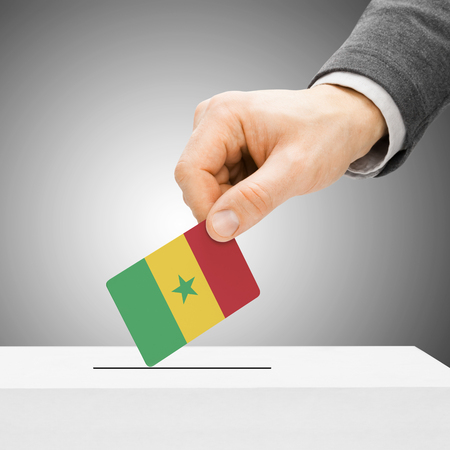 political system: Voting concept - Male inserting flag into ballot box - Senegal