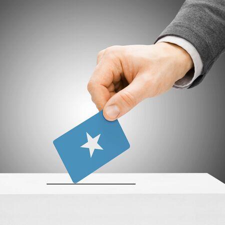 somali: Voting concept - Male inserting flag into ballot box - Somalia