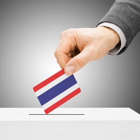 polling booth: Voting concept - Male inserting flag into ballot box - Thailand Stock Photo