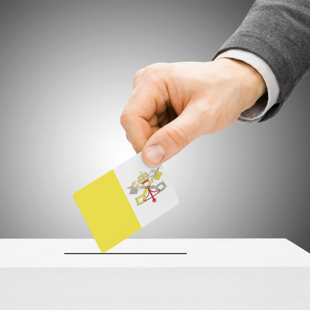 electoral system: Voting concept - Male inserting flag into ballot box - Vatican City Stock Photo