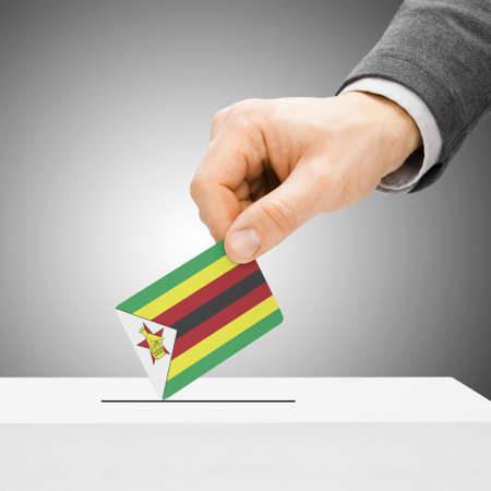 Voting concept - Male inserting flag into ballot box - Zimbabwe photo