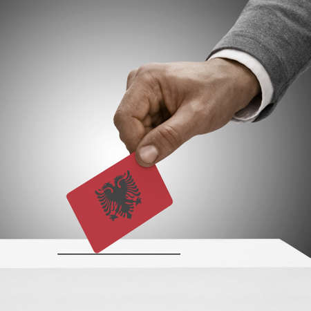 Black male holding Albania flag. Voting concept photo