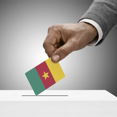 Black male holding Cameroon flag. Voting concept photo