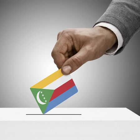 electoral system: Black male holding Comoros flag. Voting concept
