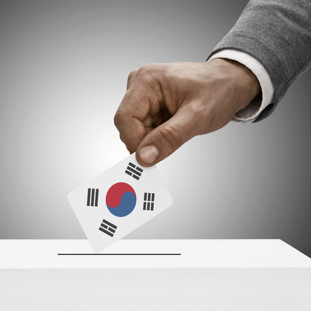 plebiscite: Black male holding South Korea flag. Voting concept