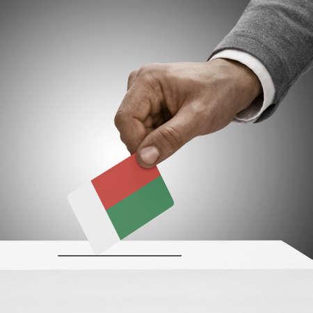political system: Black male holding flag. Voting concept - Madagascar