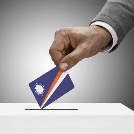 political system: Black male holding Marshall Islands flag. Voting concept Stock Photo