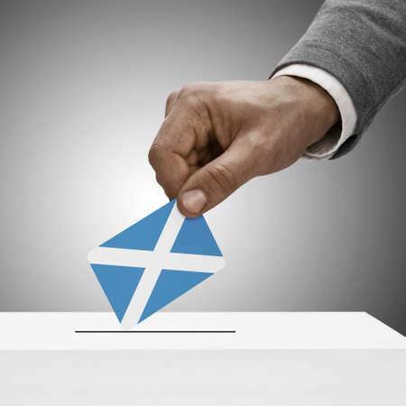 scottish parliament: Black male holding Scotland flag. Voting concept  Stock Photo