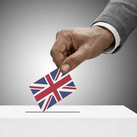 encuestando: Macho negro que sostiene la bandera de Reino Unido. Concepto de votación