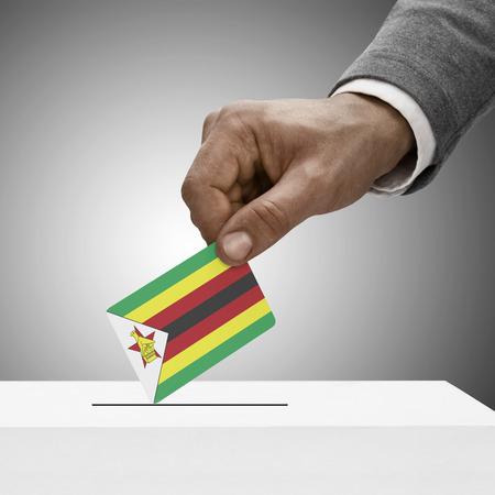 Black male holding Zimbabwe flag. Voting concept